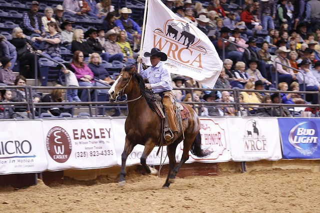 Longtime arena crew member Steve Lewis presents the WRCA colors during the Thursday night  opening ceremonies. He's riding his good horse Peppy Will Pep.